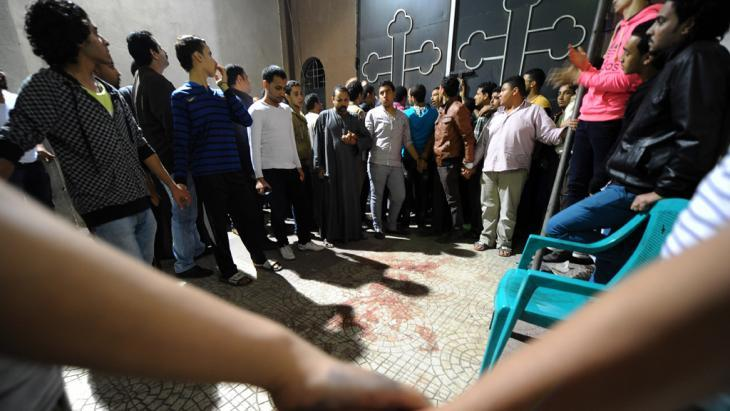 مصريون متجمعون عند كنيسة قبطية في القاهرة بتاريخ 20 أكتوبر/ تشرين الأول 2013 بعد مقتل امرأة وإصابة آخرين برصاص رجل يركب دراجة نارية. photo: AP/Mohsen Nabil