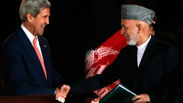 الرئيس الأفغاني كرزاي ووزير الخارجية الأمريكي كيري في كابل بعد إعلانهما نتائج الاتفاقية الأمنية بينهما في 12 أكتوبر/ تشرين الأول 2013. photo: Mohammad Ismail/Reuters