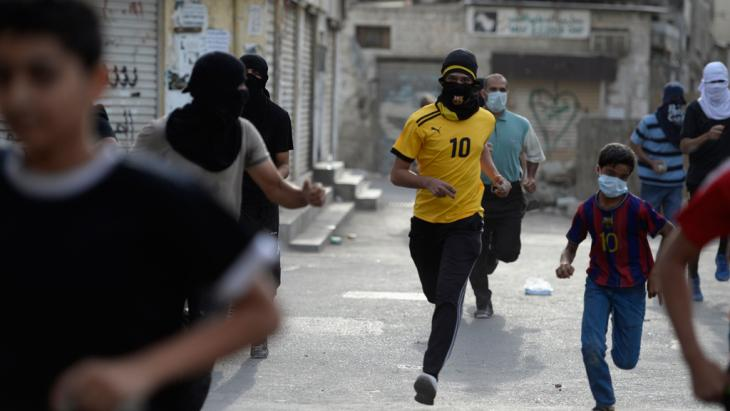 Protesters run for cover from tear-gas fired by riot-police during clashes in the village of Jidhafs, west of Manama, April 20, 2013 (photo: Reuters)