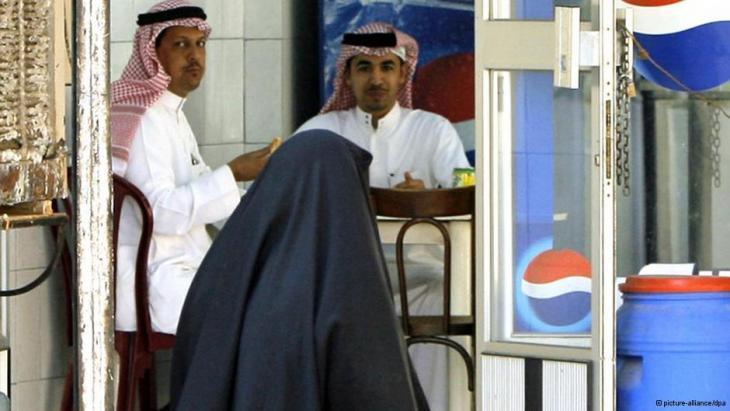 امرأة منقبة في مدينة جدة السعودية تمر بجوار مقهى يجلس فيه بعض الرجال.   Foto: picture-alliance/dpa