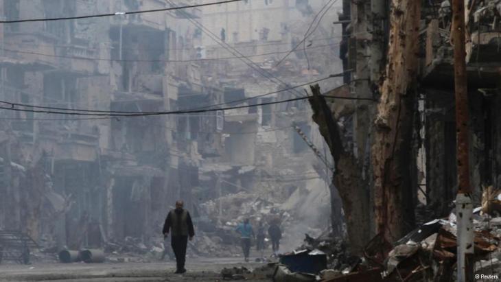 رجل يمشي وحوله أنقاض البنايات في أحد شوارع مدينة دير الزور السورية. photo: Reuters