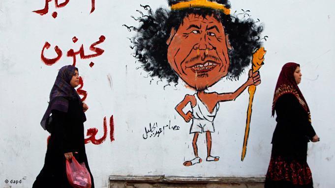 جدارية يظهر عليها رسم كاريكاتوري للزعيم الليبي الراحل معمر القذافي ومكتوب فيها: أكبر مجنون في العالم. photo: EPA/Getty Images