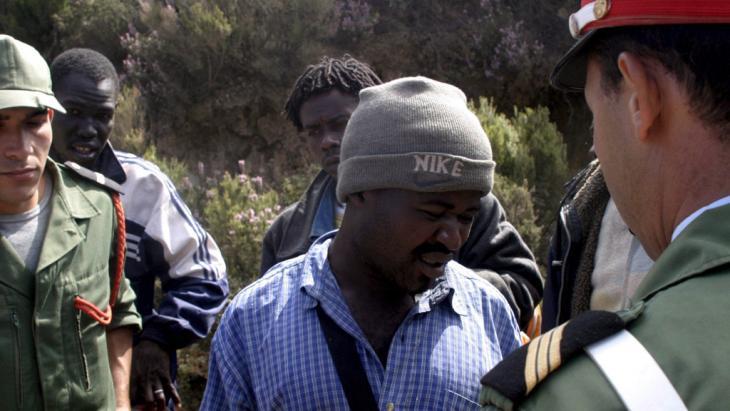 عناصر الأمن المغربي يحتجزون لاجئين أفارقة حاولوا اجتياز الحاجز الشائك الذي يفصل الأراضي المغربية عن مدينة سبتة الإسبانية الواقعة على امتداد الأراضي المغربية في شمال إفريقيا. photo: picture-alliance/dpa/dpaweb