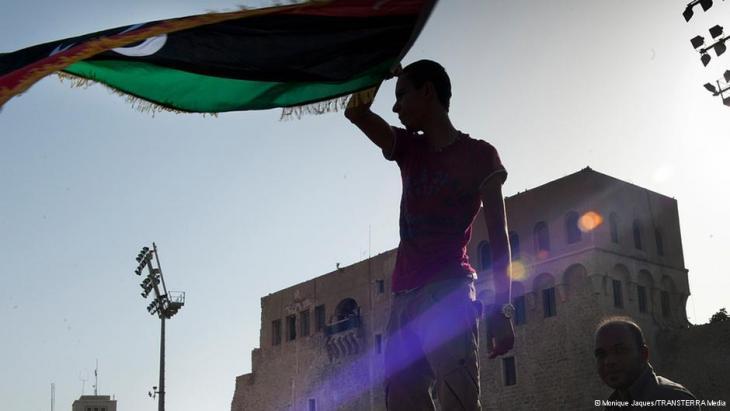 شاب يلوح بالعلم الليبي