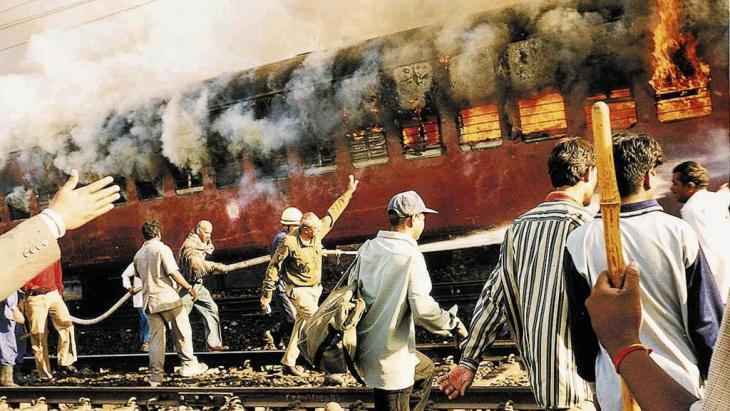 قطار محترق في محطة قطار جودهرا في فبراير/ شباط 2002. Foto: AP