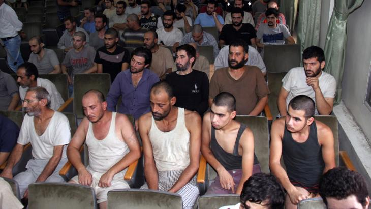 سجناء سوريون قبل الإفراج عنهم في قاعة محكمة في دمشق في 1 أيلول/سبتمبر 2012.  photo: Bassem Tellawi/AP/dapd