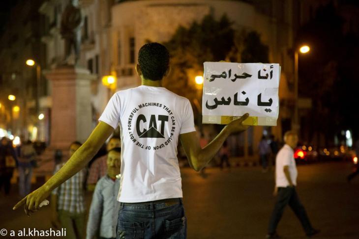 يرفع شاب لافتة وهو يبيع في منتصف في القاهرة. A. Alkhashali