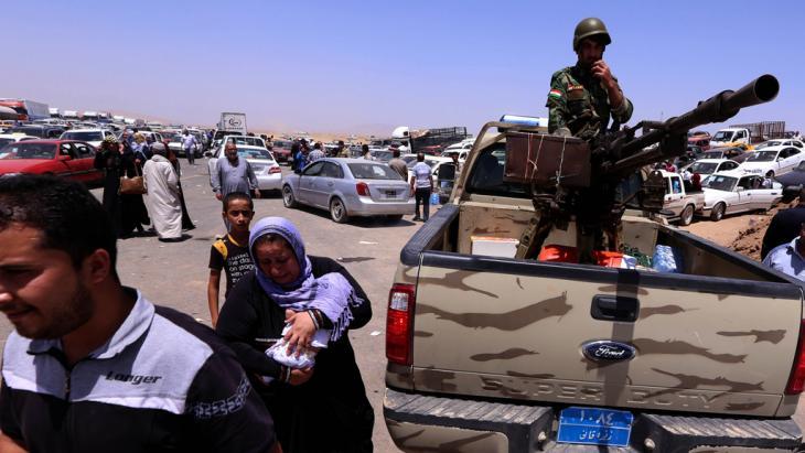 Flüchtlinge aus Mossul und Kämpfer der kurdischen Peschmerga am Checkpoint in Aski Kalak; Foto: Safin Hamed/AFP/Getty Images