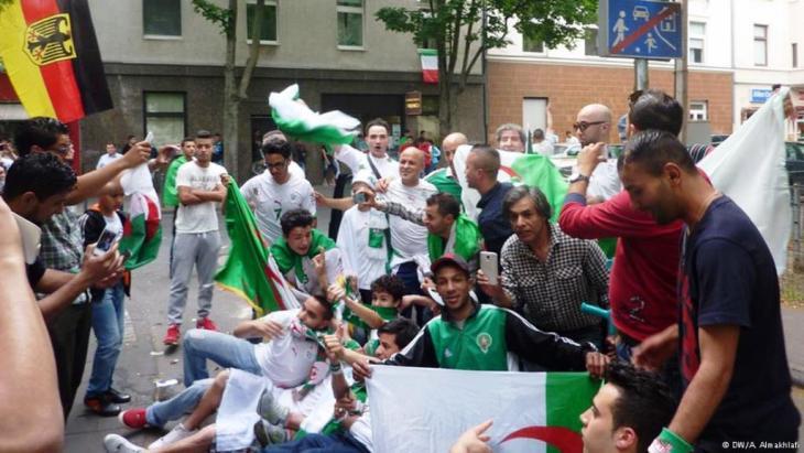 فرحة بعد تسجيل الهدف الجزائري والعلم الألماني حاضر إلى جانب العلم الجزائري في كولونيا
