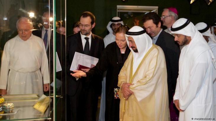 Ulrike Al-Khamis zeigt dem Herrscher Sharjahs, Scheich Sultan bin Mohammad al Qasimi einige der Exponate der Ausstellung; Foto: sharjahmuseums.ae