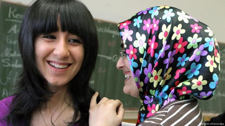 Muslim women, one wearing a brightly coloured headscarf, laughing in front of a blackboard in a classroom. Photo: dpa