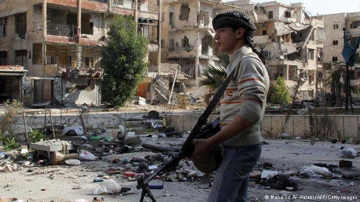مقاتل شاب أمام منازل مدمرة في سوريا. Foto: AFP/Getty Images