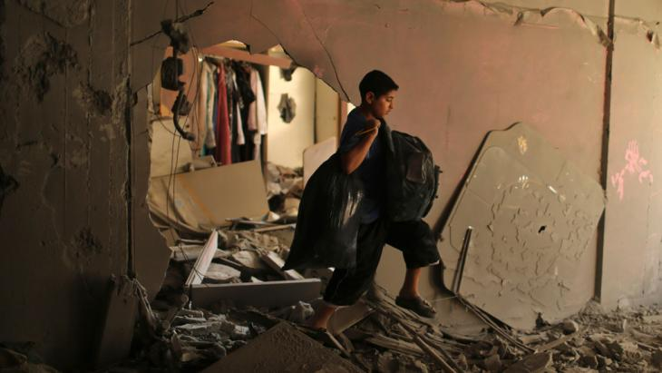 A Palestinian boy carries his belongings inside his family's ruined house in Gaza City, July 16, 2014. REUTERS/Mohammed Salem
