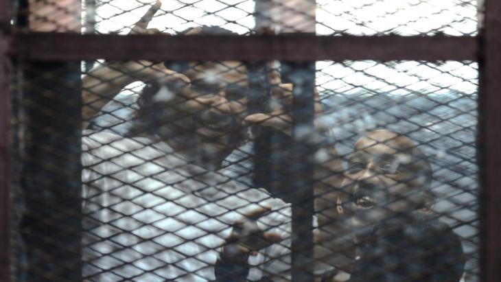 علاء عبد الفتاح وأحد رفاقه في قفص الاتهام في إحدى محاكم القاهرة. Foto: Getty Images/AFP