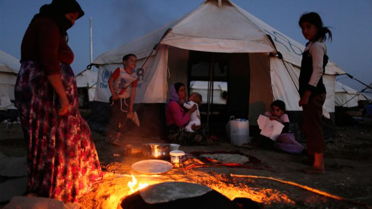 A Yazidi woman, who fled violence in the Iraqi town of Sinjar, makes bread at Bajed Kadal refugee camp in Dohuk province, 22 August 2014 (photo: Reuters/Youssef Boudlal)