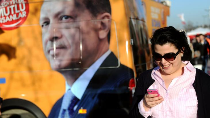 A Turkish woman in front of an image of President Erdogan (photo: OZAN KOSE/AFP/Getty Images)