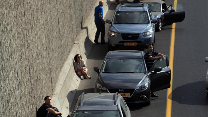 إسرائيليون يحتمون بالقرب من سياراتهم بعد انطلاق صافرات الإنذار بمدينة تل أبيب في التاسع من يوليو 2014. (photo: picture-alliance//Landov)