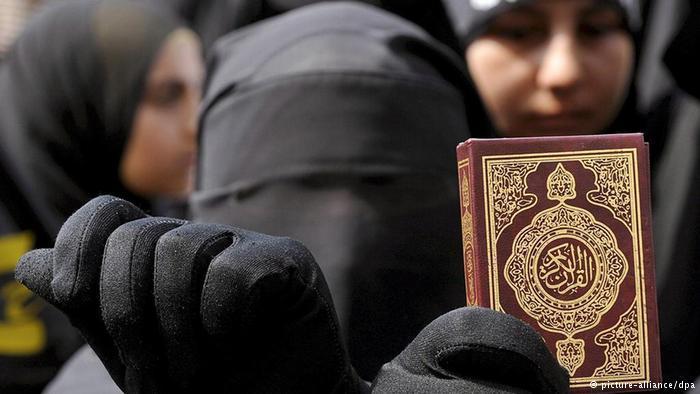 Frau mit Niqab hält eine Koranausgabe; Foto: dpa/picture-alliance