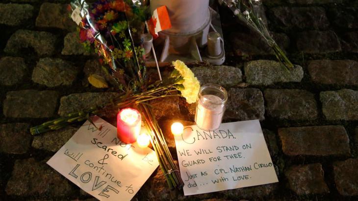 شموع وورود عند النصب التذكاري الوطني في أوتاوا بعد مقتل جندي على يد مايكل  زيهاف–بيبو، وهو مواطن كندي تحول للإسلام. وتسبب الهجوم الذي وقع في الثاني والعشرين من تشرين أول/ أكتوبر 2014 في مقتل أحد الجنود كما قتل المهاجم في تبادل لإطلاق النار مع الشرطة. (photo: AP Photo/The Canadian Press, Patrick Doyle)