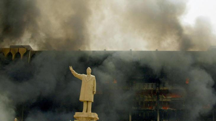 Saddam-Statue vor dem brennenden Irakischen Olympischen Komitee in Bagdad am 9. April 2003; Foto: AFP/picture-alliance