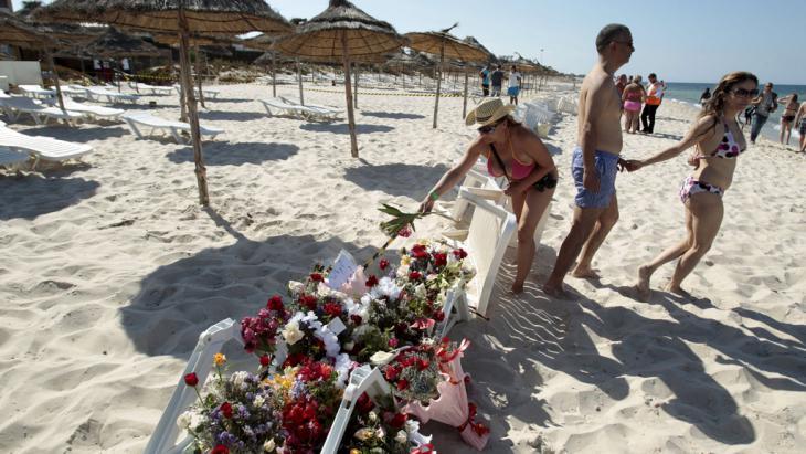 """Menschen legen Blumen am Anschlagsort in der Nähe des """"Imperial Marhaba Hotels"""" nieder; Foto: Reuters/Z. Souissi"""