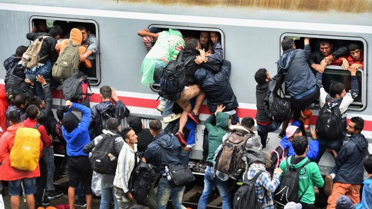لاجئون يحاولون الصعود إلى قطار مزدحِم في كرواتيا. Foto: Getty Images/J. J. Mitchell