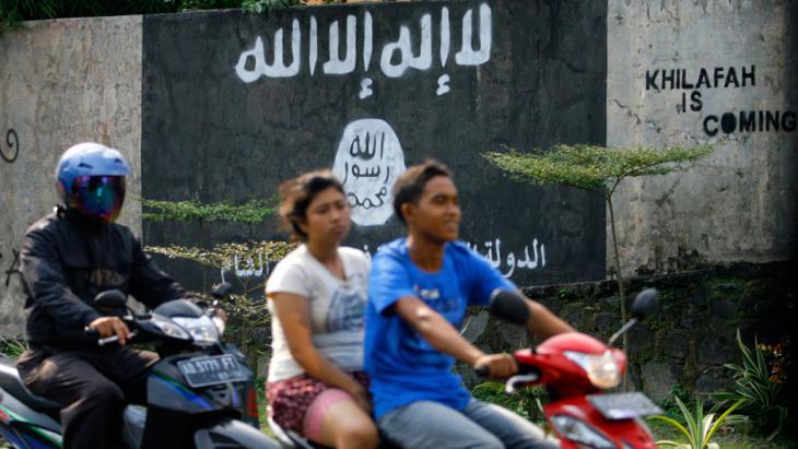 """شاب يقود دراجته النارية وخلفه امرأة وعلى الحائط رمز تنظيم """"الدولة الإسلامية"""" إندونيسيا.  (photo: picture-alliance/AP)"""