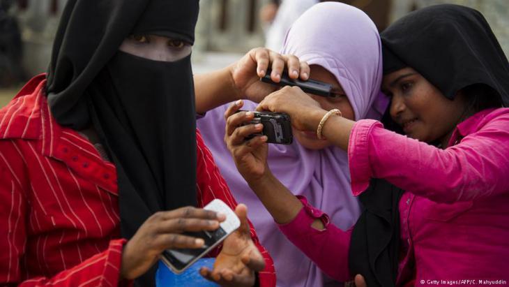 نساء يحملن الهاتف المحمول.