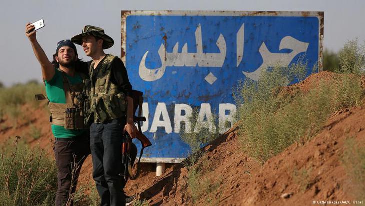 عنصران من الجيش السوري الحر يلتقطان سيلفي على مدخل مدينة جرابلس.