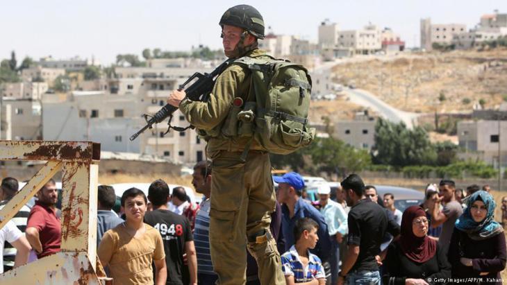 جندي إسرائيلي يحرس نقطة تفتيش جنوب الخليل.