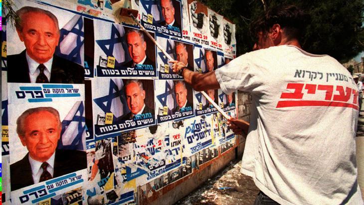 Ein Aktivist des rechten Likud überklebt Wahlplakate des israelischen Ministerpräsidenten Schimon Peres am 26.5.1996 in Jerusalem mit denen des Likud-Führers Benjamin Netanjahu; Foto: picture-alliance/COLORplus/P. Guyot