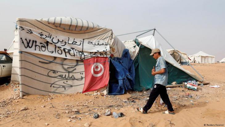 متظاهر تونسي يمشي قرب خيمته خلال اعتصام عند حقل الكامور النفطي، مطالبا بتوفير فرص العمل وحصة من عائدات الموارد الطبيعية في المنطقة بالقرب من بلدة تطاوين، تونس 11 مايو/ أيار 2017. (photo: Reuters/Zoubeir Souissi)
