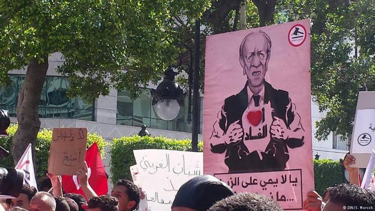 """′""""أنا أحب الفساد """": كاريكاتورية للرئيس التونسي الباجي السبسي، في مظاهرة """"مانيش مسامح"""" على شارع الحبيب بورقيبة في تونس، 13 مايو/ أيار 2017. (photo: DW/Sarah Mersch)"""