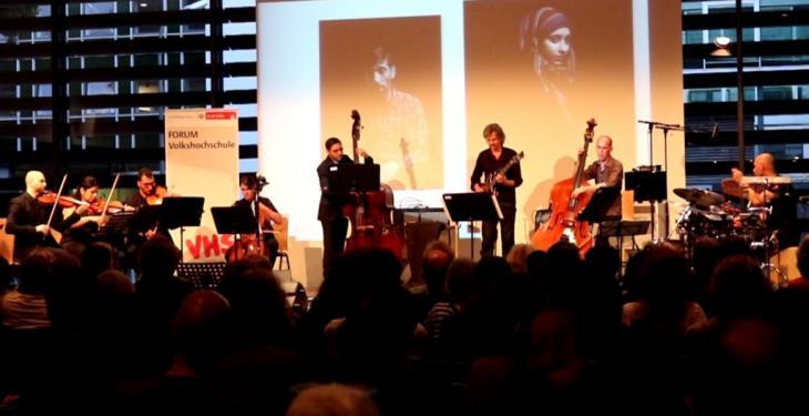 جمهور عربي وألماني في كولونيا يشاهد ويستمع إلى نغمات خماسي دمشق الوتري مع عازفين غربيين من ألمانيا وكندا والنرويج وهولندا وفي الخلفية صورتان تعبران عن معاناة اللاجئين.  Ali Almakhlafi ©
