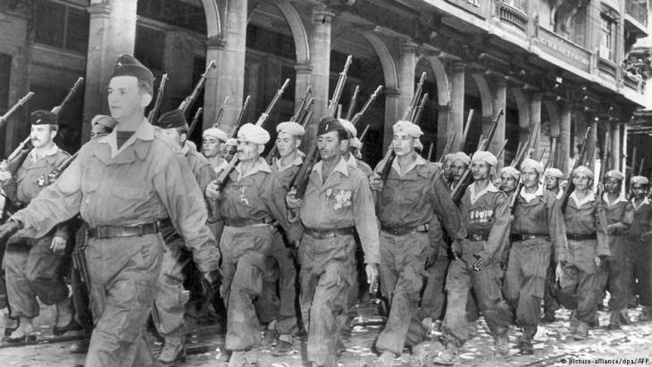 """حركيون يمشون في شوارع الجزار عام 1957. و""""الحركيون"""" هم جزائريون مسلمون جندهم الجيش الفرنسي واستعملتهم فرنسا من أجل قمع الثوار الجزائريين والتجسس عليهم."""