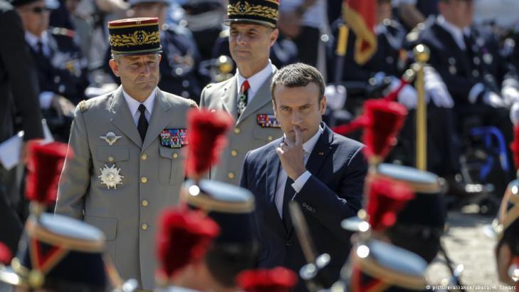 الرئيس الفرنسي إيمانويل ماكرون عند قصر الإيليزيه في باريس وإلى جانبه جنرالان فرنسيان.