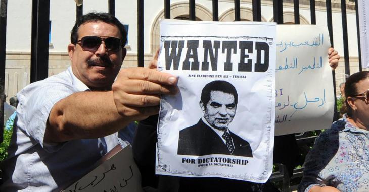 """تونسي يحمل لافته مكتوب عليها بالإنكليزية """" مطلوب: بن علي - تونس"""". Foto: AFP"""