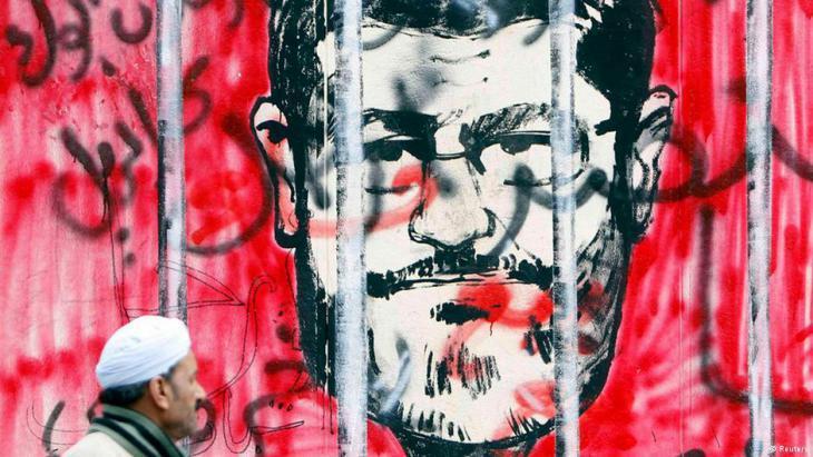 جدارية عليها رسم يُظهِر رئيس مصر الأسبق محمد مرسي خلف القضبان. Foto: Reuters
