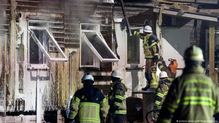 صورة لمبنى محترق وبجانبه عناصر الإطفاء