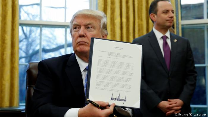 دونالد ترامب وهو يوقع قرارات تنفيذيه بُعيد تسلمه الرئاسة الأمريكية