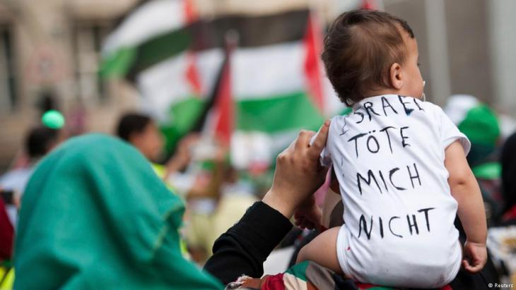 """طفل يحمل عبارة """"إسرائيل.. لا تقتليني"""" في مظاهرة ببرلين"""