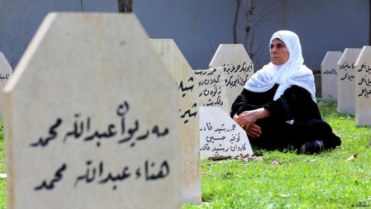 امرأة جالسة بين قبور ضحايا حلبجة - كردستان العراق.  Foto: Reuters