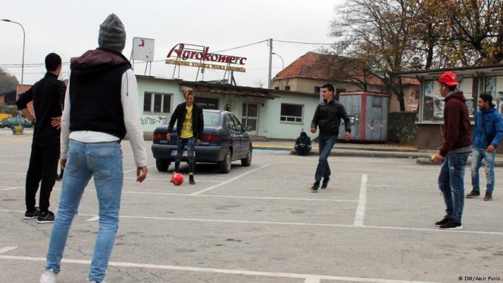 مهاجرون شباب يلعبون كرة القدم أمام محطة الحافلات في فليكا كلادوسا - البوسنة والهرسك