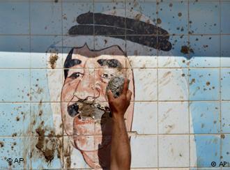 بعد سقوط نظام صدام حسين - كردي في تاريخ 10 / 04 / 2018 وهو يحطم صورة لصدام حسين في شمال العراق.  Foto: AP
