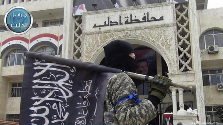 مقاتلون من جبهة النصرة أمام المبنى الإداري المركزي لمحافظة إدلب السورية. Foto: AP/picture-alliance