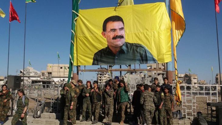 """وحدات من """"قوات سوريا الديمقراطية"""" أمام صورة أوجلان بعد سيطرتهم على الرقة في 19 أكتوبر / تشرين الاول 2017. Foto: AFP/Getty Images"""