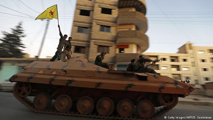 مقاتلون من وحدات حماية الشعب الكردية السورية على سيارة مصفحة في مدينة القامشلي في شمال شرق سوريا على الحدود التركية. Foto: AFP/Getty Images