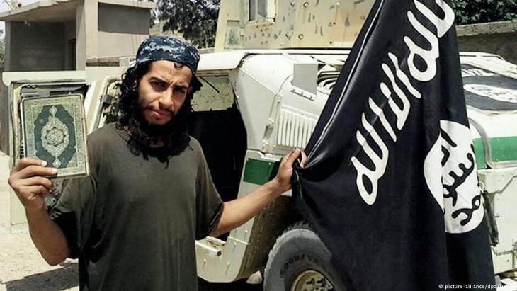 """متطرف يحمل راية """"داعش"""" والقرآن في يديه. Foto: picture-alliance/dpa"""
