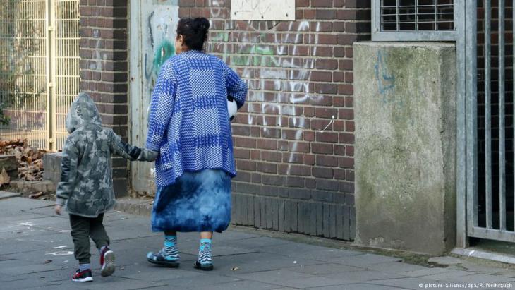 امرأة وطفل يمشيان ويمران بمنزل متهالك في حي ماركسلوه بمدينة دويسبورغ - ألمانيا 20 / 12 / 2016. (photo: Roland Weihrauch/dpa)