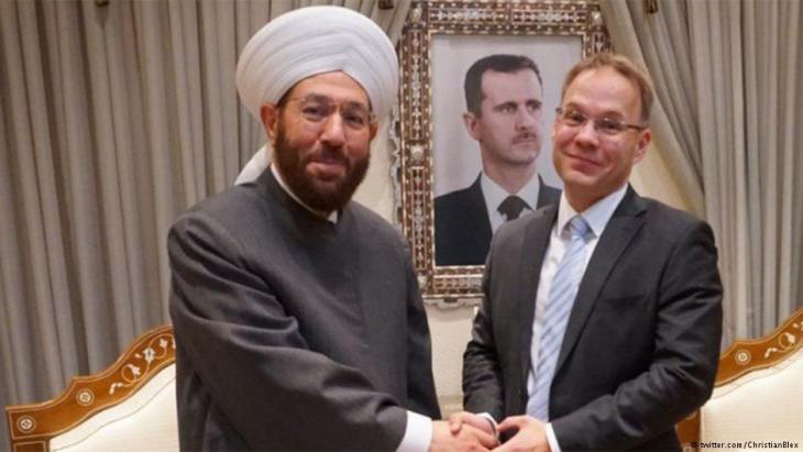 """المفتي الأعلى في دمشق أحمد حسون يصافح رئيس وفد نواب """"البديل من أجل ألمانيا"""" كريستيان بليكس."""